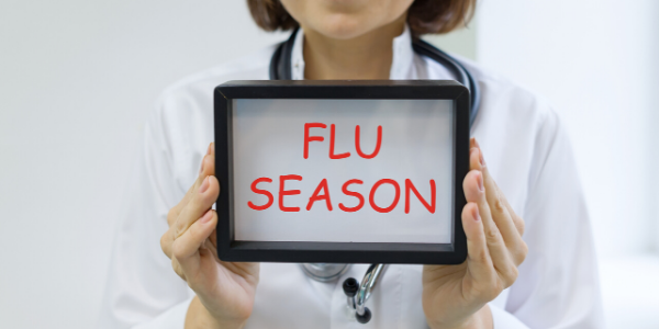 doctor holding sign that says flu season
